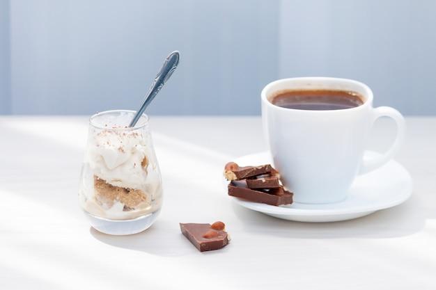 Kopje koffie, melkchocolade met noten, ijs met chocoladepoeder