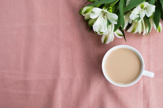 Kopje koffie met boeket bloemen op tafel. samenstelling van het ochtendontbijt