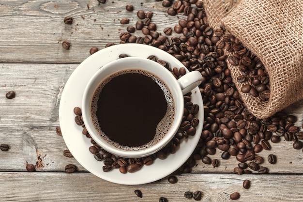 Kopje koffie met bonen op tafel