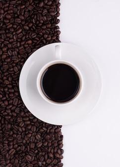 Kopje koffie met bonen op witte achtergrond