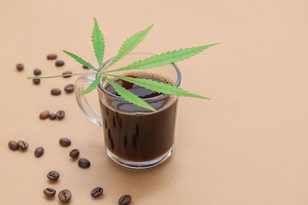 Kopje koffie met cannabis blad en geroosterde bonen op neutrale beige achtergrond