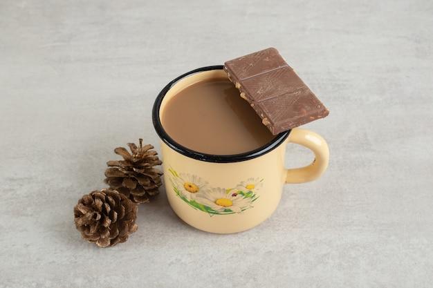 Kopje koffie met dennenappels en chocoladereep