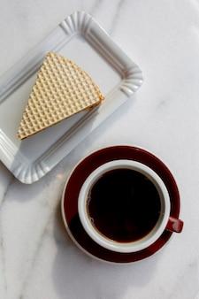 Kopje koffie met dessert op de marmeren tafel. koffiedag. ontbijt op een witte achtergrond. warme drank met cake. aromatische koffie bovenaanzicht. zwarte koffie met eten. ontbijt in een café. voedsel dag