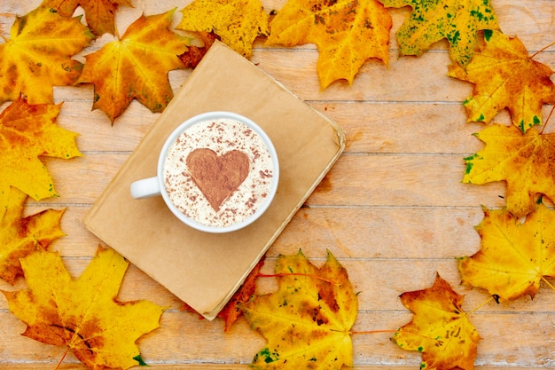 Kopje koffie met een hart van kaneel en boek op tafel, esdoornbladeren rond