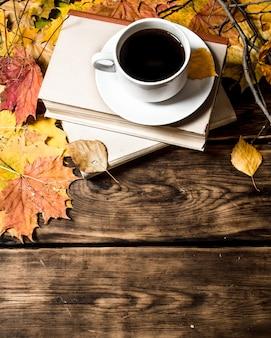 Kopje koffie met een oud boek en esdoornbladeren op houten achtergrond