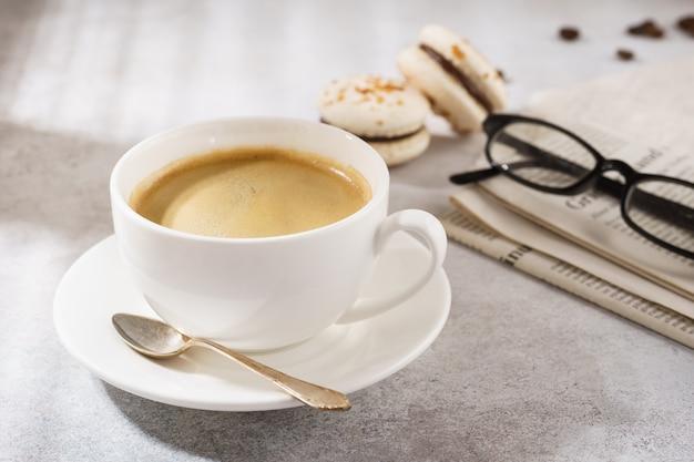 Kopje koffie met franse macarons, krant en glazen.