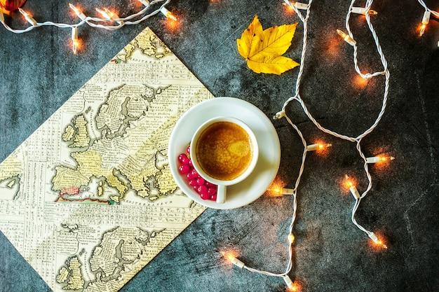 Kopje koffie met gele bladeren geografische kaart en gloeiende slinger op een betonnen achtergrond