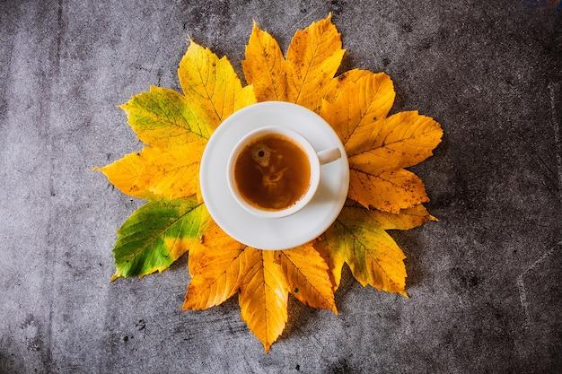 Kopje koffie met gele bladeren op een betonnen achtergrond herfstdecoratie