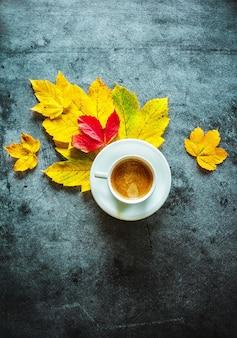 Kopje koffie met gele en rode bladeren op een betonnen achtergrond herfstdecoratie