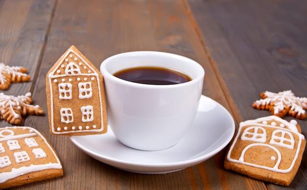 Kopje koffie met handgemaakte koekjes huizen en sneeuwvlokken