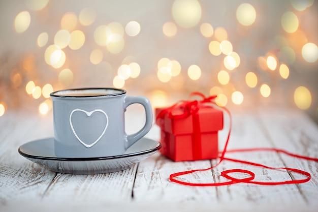 Kopje koffie met hart en rode huidige doos, concept valentijnsdag,