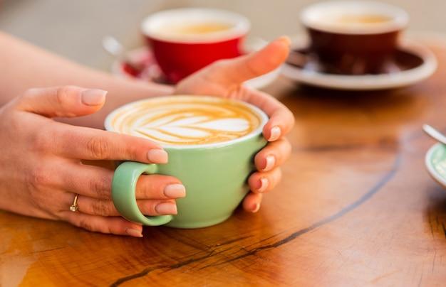 Kopje koffie met hartvorm. goedemorgen koffie. barista serveert koffie. ochtendvibes in café. hart latte kunst. vrouw houdt warme kop koffie met hartvorm. latte kunst op houten tafel.