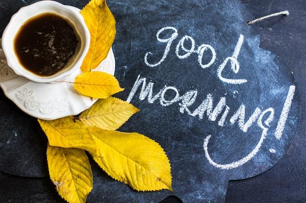 Kopje koffie met herfstbladeren als seizoensgebonden concept