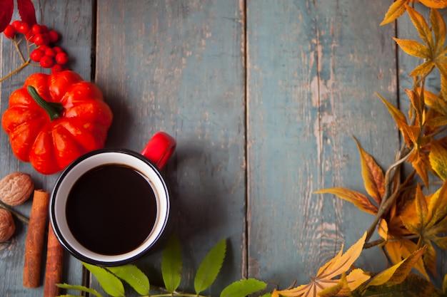 Kopje koffie met herfstbladeren en kleine pompoenen