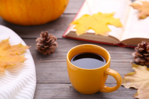 Kopje koffie met herfstbladeren en oud boek op grijze achtergrond
