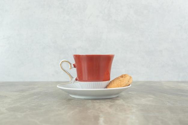 Kopje koffie met koekje op marmeren tafel.