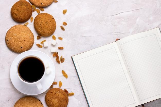Kopje koffie met koekjes en een dagboek van het ontbijt-concept