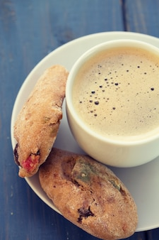 Kopje koffie met koekjes op blauwe houten tafel