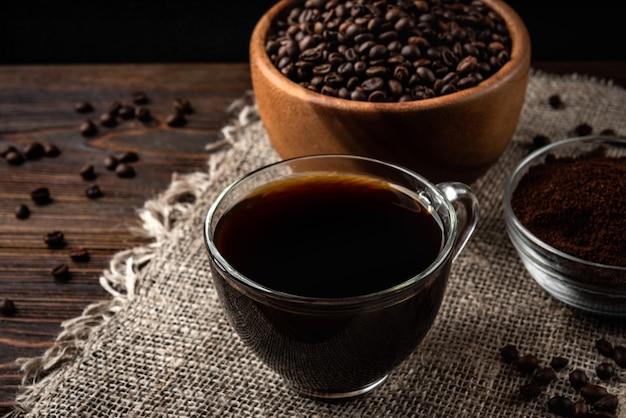 Kopje koffie met koffiebonen en poeder op donkere houten ondergrond