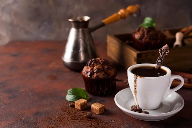 Kopje koffie met koffiebonen, houten kist met koffiekorrels en specerijen,