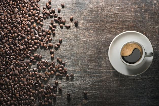 Kopje koffie met koffiebonen op oude tafel