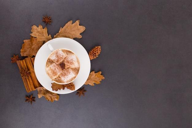 Kopje koffie met marshmallows en cacao, bladeren, gedroogde sinaasappels, kaneel en steranijs, grijze stenen achtergrond. lekkere warme herfstdrank. copyspace.