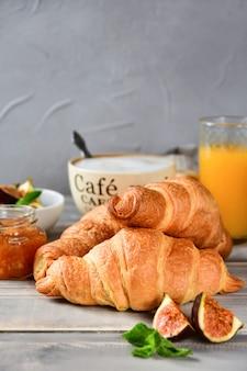 Kopje koffie met melk en croissants op een houten tafel.