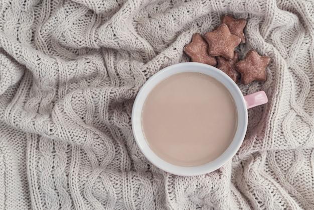 Kopje koffie met melk en stervormige gemberkoekjes op warme gebreide beige deken.
