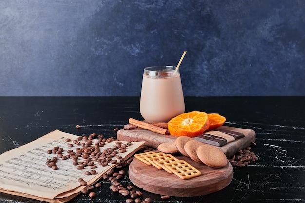 Kopje koffie met melk en stukjes sinaasappel.