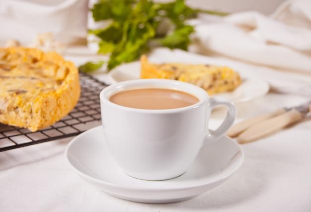 Kopje koffie met melk met zelfgemaakte vers smakelijke franse quiche lorraine taart met kippenvlees en champignons.