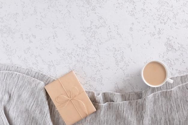 Kopje koffie met melk op witte gestructureerde achtergrond met warme grijze plaid, kopie ruimte. plat lag, bovenaanzicht