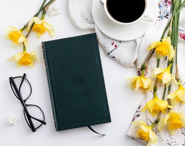 Kopje koffie met mooie gele bloemen, een zwart notitieboekje en een bril op witte achtergrond