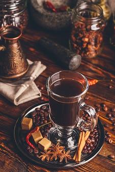 Kopje koffie met oosterse kruiden op metalen dienblad. cezve en enkele potten op achtergrond.