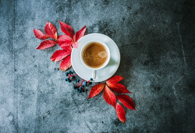 Kopje koffie met rode herfstbladeren en bessen op een betonnen ondergrond