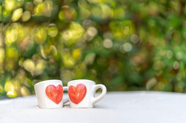 Kopje koffie met rood hart gedrukt op zand tegen natuur bokeh achtergrond.