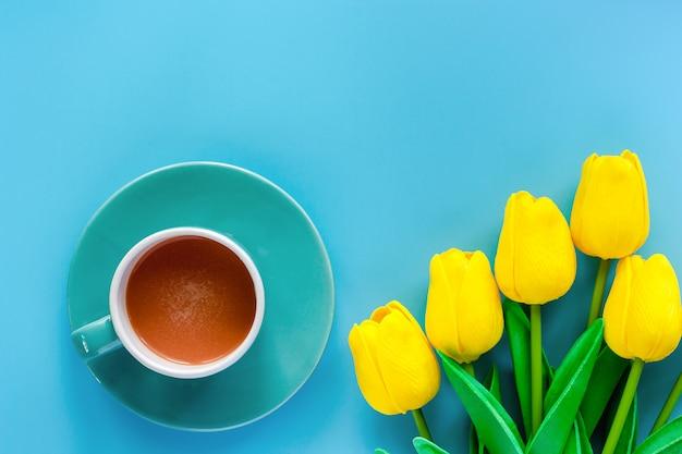 Kopje koffie met schotel en kunstmatige gele tulpen op blauwe achtergrond