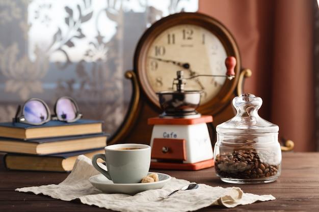 Kopje koffie met schotel met zak met koffiebonen op zwart