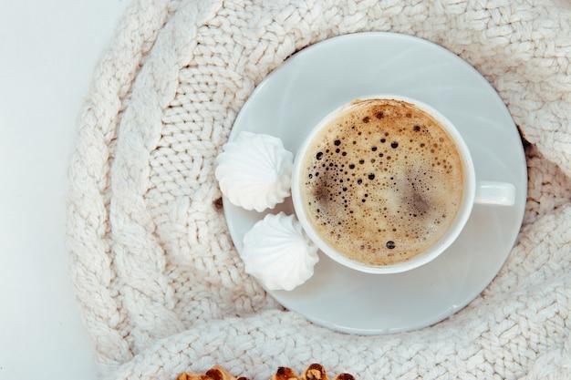 Kopje koffie met schuimgebak en gebreide trui - bovenaanzicht.