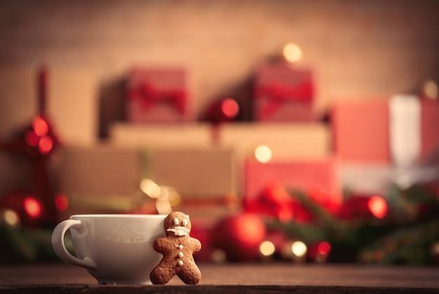 Kopje koffie met speculaaspop en kerstcadeau op houten tafel