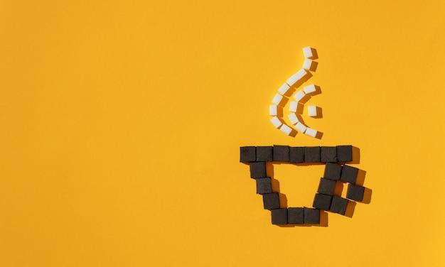 Kopje koffie met stoom gemaakt met kolen en suikerklontjes op gele achtergrond.