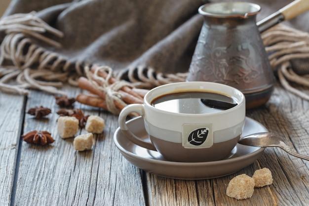 Kopje koffie met suiker en specerijen en een houten doos met korrels van koffie op een houten bord