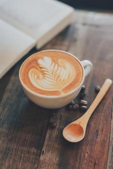 Kopje koffie met tekenen op het schuim en een boek