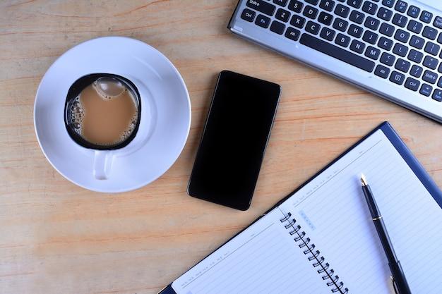 Kopje koffie met toetsenbord en muis, vulpen, notitieboekje, rekenmachine en smartphone op tafel