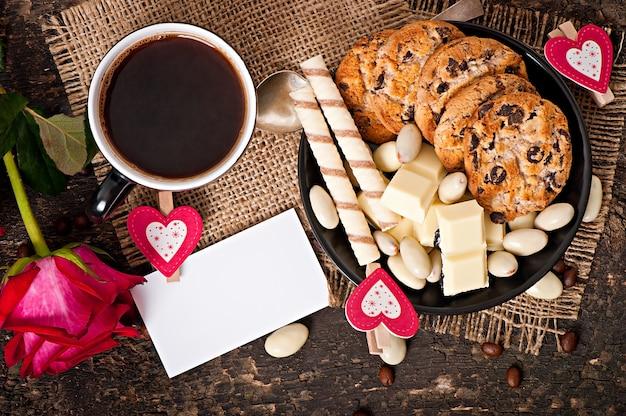 Kopje koffie met witte chocolade, amandelen en koekjes