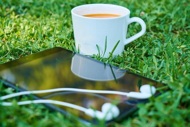 Kopje koffie naast een mobiel met een koptelefoon
