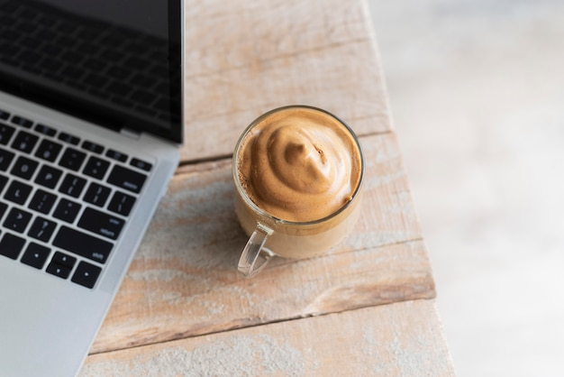 Kopje koffie naast laptop