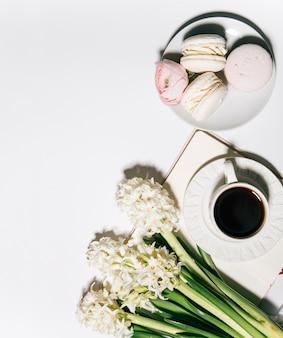 Kopje koffie notebook en lente bloemen op witte achtergrond bovenaanzicht close-up