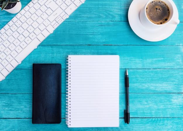 Kopje koffie, notebooks, pen op turquoise houten bureau