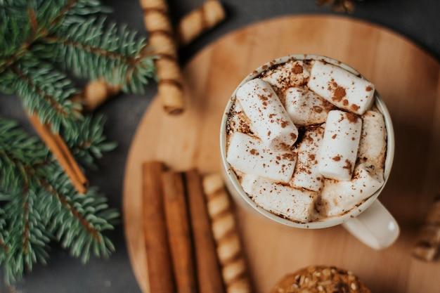 Kopje koffie of cacao met marshmallows, kaneelstokjes en koekjes op een houten bord