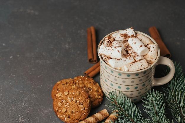 Kopje koffie of cacao met marshmallows, takken van een kerstboom